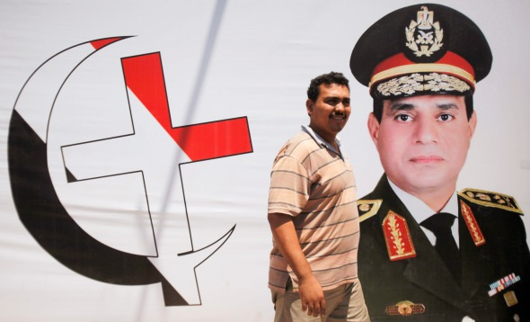 An anti-Mursi supporter of Egypt's army walks in front of his shop, with huge posters of Egypt's army chief General Abdel Fattah al-Sisi with cross and crescent symbol of the unity Egyptians in downtown Cairo
